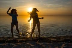 Två härliga flickor, studenter dansar på stranden på solnedgången Arkivfoton