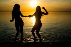 Två härliga flickor, studenter dansar på stranden på solnedgången Arkivbild