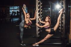 Två härliga konditionunga flickor som sträcker i idrottshall extrem sträckning Royaltyfria Bilder