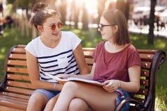 Två härliga kvinnliga studenter bär sommarskuggor, vilar på bänk parkerar, har in positiva uttryck, cramm för examen, diskuterar  arkivbild
