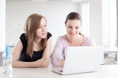 Två härliga kvinnliga studenter som arbetar på bärbara datorn Arkivfoton