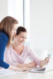 Två härliga kvinnliga studenter som arbetar på bärbara datorn Royaltyfria Bilder