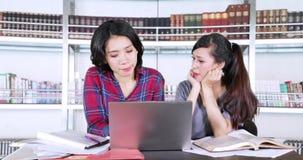 Två härliga kvinnliga studenter som tillsammans studerar lager videofilmer