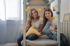 Två härliga kvinnliga vänner har gyckel inomhus Kvinnligt kamratskap Fotografering för Bildbyråer