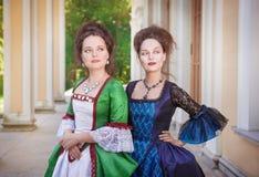 Två härliga kvinnor i medeltida klänningar Arkivfoto