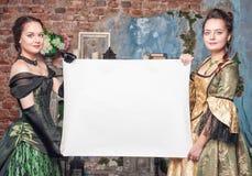 Två härliga kvinnor i medeltida klänningar med tomt papper Royaltyfri Foto