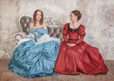 Två härliga kvinnor i medeltida klänningar på soffan Fotografering för Bildbyråer