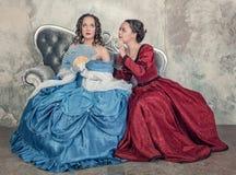 Två härliga kvinnor i medeltida klänningar skvallrar på soffan Arkivfoto
