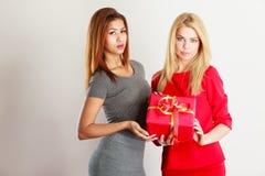 Två härliga kvinnor med den röda gåvaasken Royaltyfria Bilder