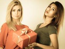 Två härliga kvinnor med den röda gåvaasken Arkivfoton