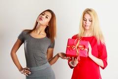 Två härliga kvinnor med den röda gåvaasken Royaltyfria Foton