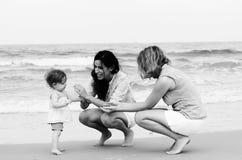 Två härliga kvinnor med en behandla som ett barn Arkivbilder