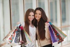 Två härliga kvinnor med shoppingpåsar bredvid en supermarket Royaltyfri Foto