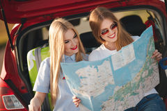 Två härliga kvinnor reser på en röd bil royaltyfri foto
