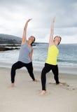 Två härliga kvinnor som öva yoga på stranden Royaltyfri Foto