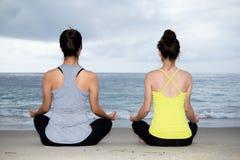 Två härliga kvinnor som öva yoga på stranden Royaltyfria Bilder