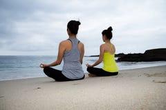 Två härliga kvinnor som öva yoga på stranden Royaltyfri Fotografi