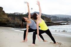 Två härliga kvinnor som öva yoga på stranden Fotografering för Bildbyråer
