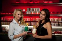Två härliga kvinnor som dricker coctailen i en nattklubb och har Royaltyfri Fotografi