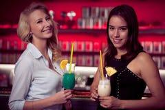 Två härliga kvinnor som dricker coctailen i en nattklubb och har Royaltyfri Bild