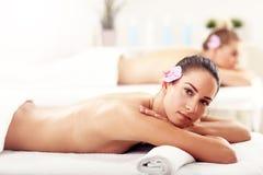 Två härliga kvinnor som får massage i brunnsort Arkivfoton