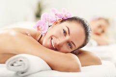 Två härliga kvinnor som får massage i brunnsort royaltyfri bild