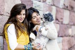 Två härliga kvinnor som kramar deras utomhus- lilla hund Royaltyfri Foto