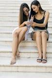 Två härliga kvinnor som ser telefonen royaltyfri fotografi
