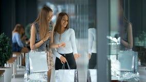 Två härliga kvinnor som shoppar och ser skyltfönster