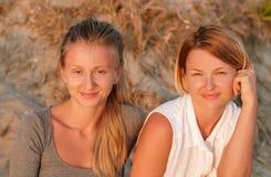 Två härliga kvinnor som sitter på sand på strandblicken på solnedgången royaltyfria foton