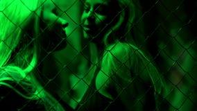 Två härliga kvinnor som står bak det chain staketet som seductively ler, passion arkivbilder