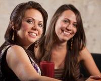 Två härliga kvinnor som tillsammans sitter arkivfoton