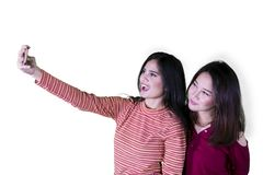 Två härliga kvinnor tar fotoet i studion royaltyfri fotografi