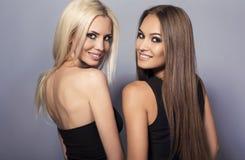 Två härliga le flickor med lyxigt hår som poserar i studio Royaltyfria Bilder