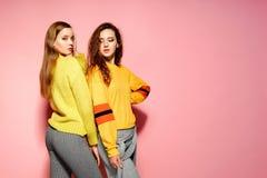 Två härliga le ursnygga flickor som ser kameran Varma kvinnor som står i stilfulla gula tröjor, på rosa färger royaltyfria foton