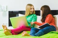 Två härliga lilla systrar som sitter på säng och lek med en minnestavla eller en bärbar dator Arkivfoton