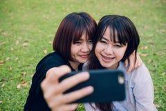 Två härliga lyckliga unga asiatiska kvinnavänner som har gyckel på, parkerar tillsammans och tar en selfie Royaltyfria Foton