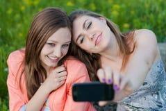 Två härliga lyckliga unga kvinnor & fototelefon Royaltyfri Foto