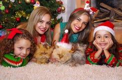 Två härliga mammor med hennes små flickor, bära julkläder, den lockiga flickan med ett rött band i hennes hår medan arkivbild