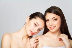 Två härliga sexiga kvinnor vad som poserar i studio och innehav laga mat med grädde Royaltyfri Foto