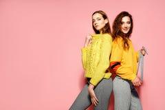 Två härliga sexiga le ursnygga flickor som ser kameran Varma kvinnor som står i stilfulla gula tröjor, på rosa färger fotografering för bildbyråer