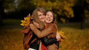 Två härliga tonårs- flickor som in kramar och rymmer en bukett av gulingsidor i Autumn Park, flickvänner som har gyckel