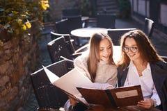 Två härliga trendiga kvinnor som sitter i gatakafét royaltyfria bilder