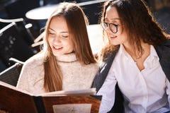 Två härliga trendiga kvinnor som sitter i gatakafét royaltyfri foto