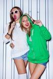 Två härliga ung flicka med röda klubbor near väggen Fotografering för Bildbyråer