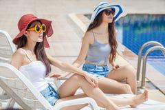 två härliga unga asiatiska kvinnor i stor sommarhatt och solglasögon som sitter på sunbed av simbassängen tillsammans lycklig fli royaltyfri foto
