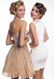 två härliga unga flickor i eleganta klänningar Royaltyfri Bild