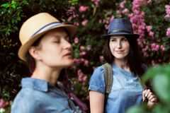 Två härliga unga flickor i jeansklänningar och hattar går till och med trädgården bland gröna träd och buskar med rosa färger Arkivfoto