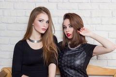 Två härliga unga flickor i svarta klänningar sitter på bänken och skvallrar Royaltyfri Fotografi