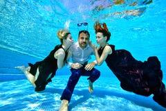 Två härliga unga flickor med bad och lek för rött och vitt hår med en ung man i ett undervattens- längst ner för vit skjorta av arkivbilder
